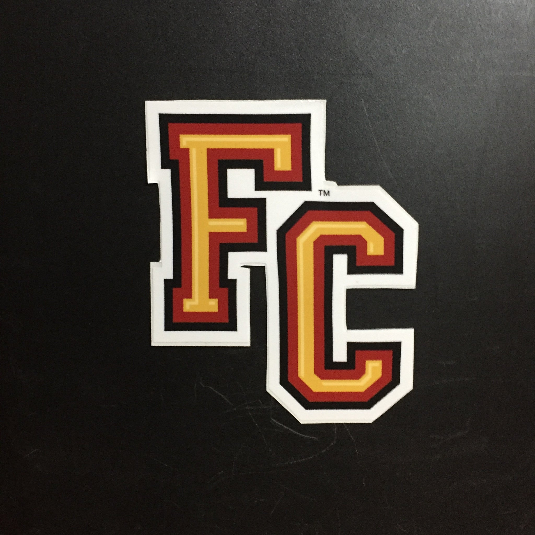 red, black and yellow F C letters decal