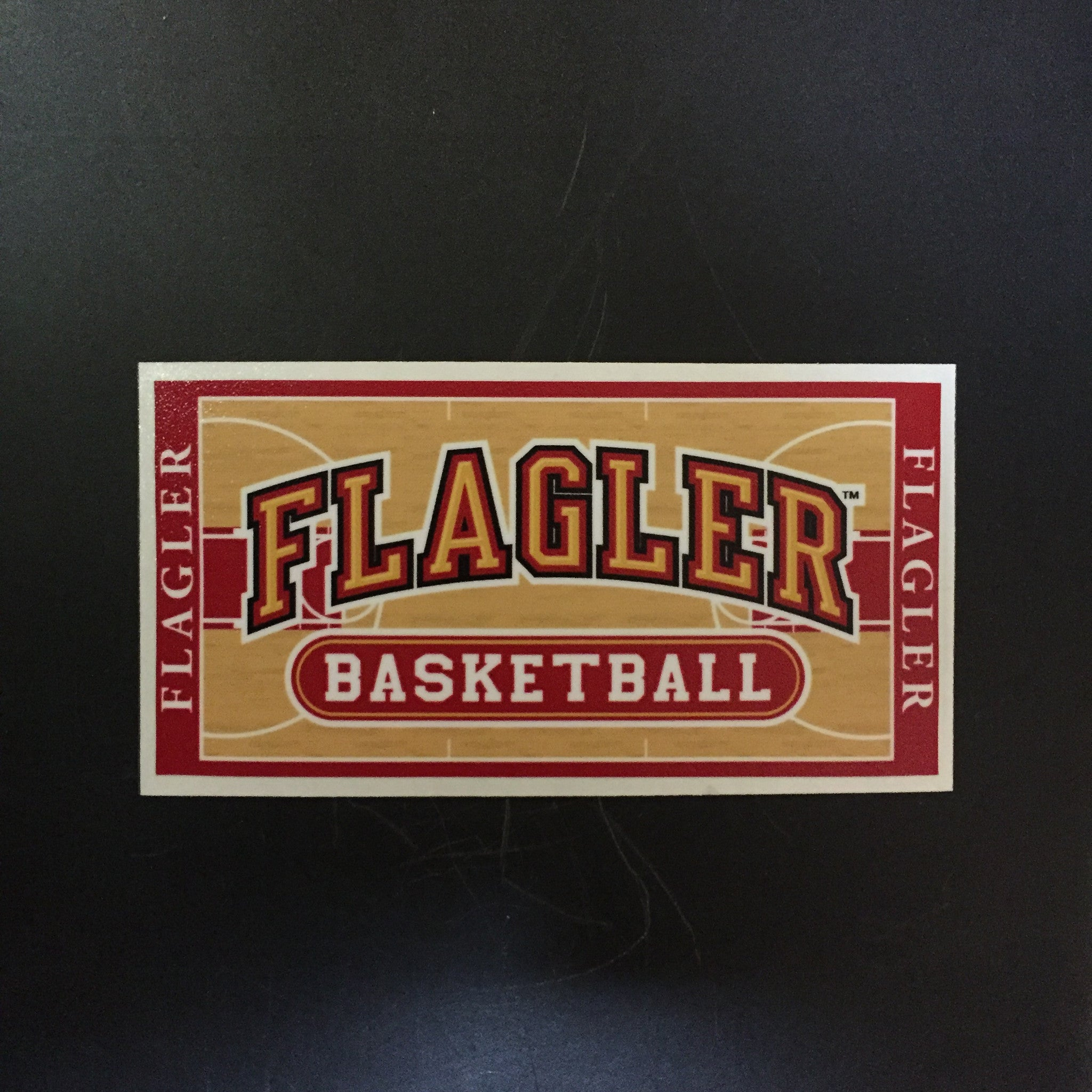 basketball court decal with Flagler written in gold and basketball written in white in red oval