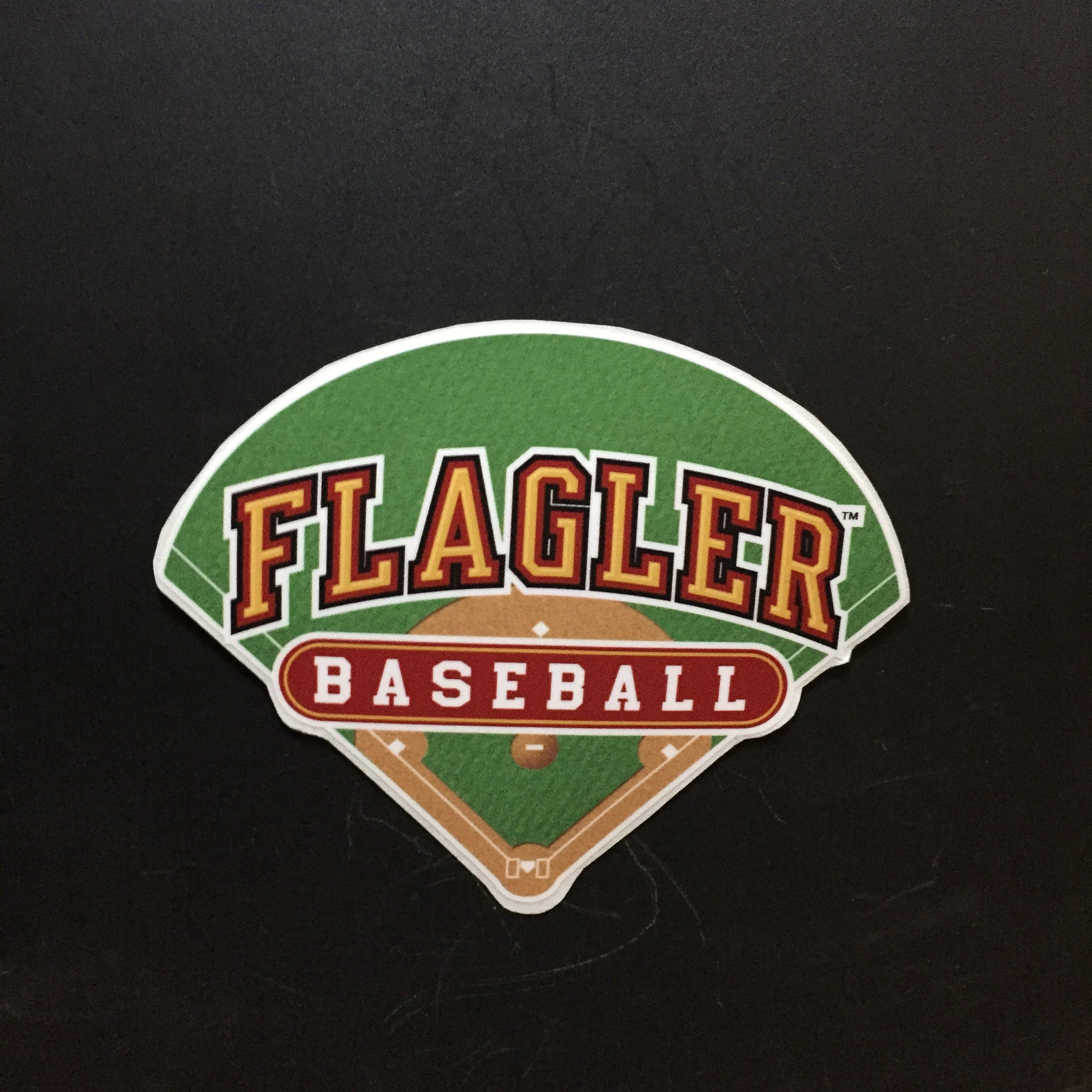baseball field decal with Flagler written in gold and baseball written in white in red oval
