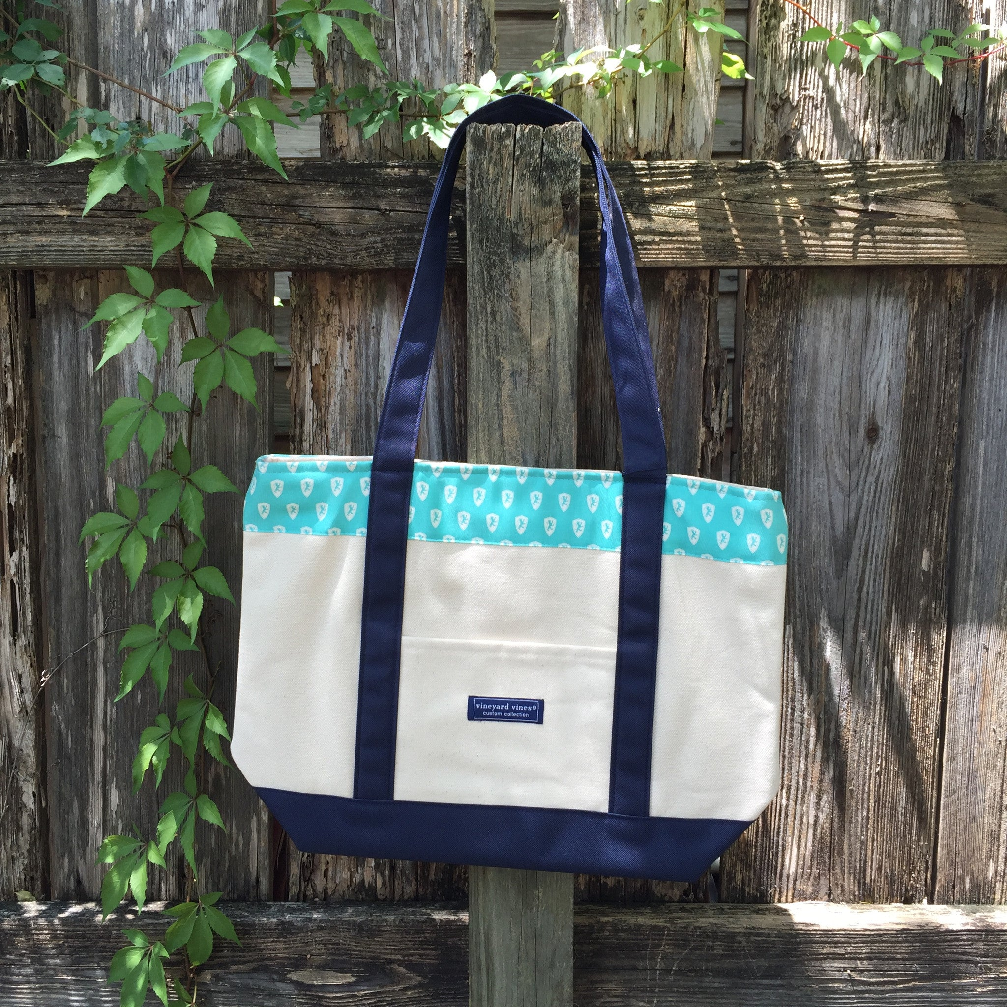 Canvas tote-bag with a baby blue section with a pattern of white lion shields. the handles are dark blue