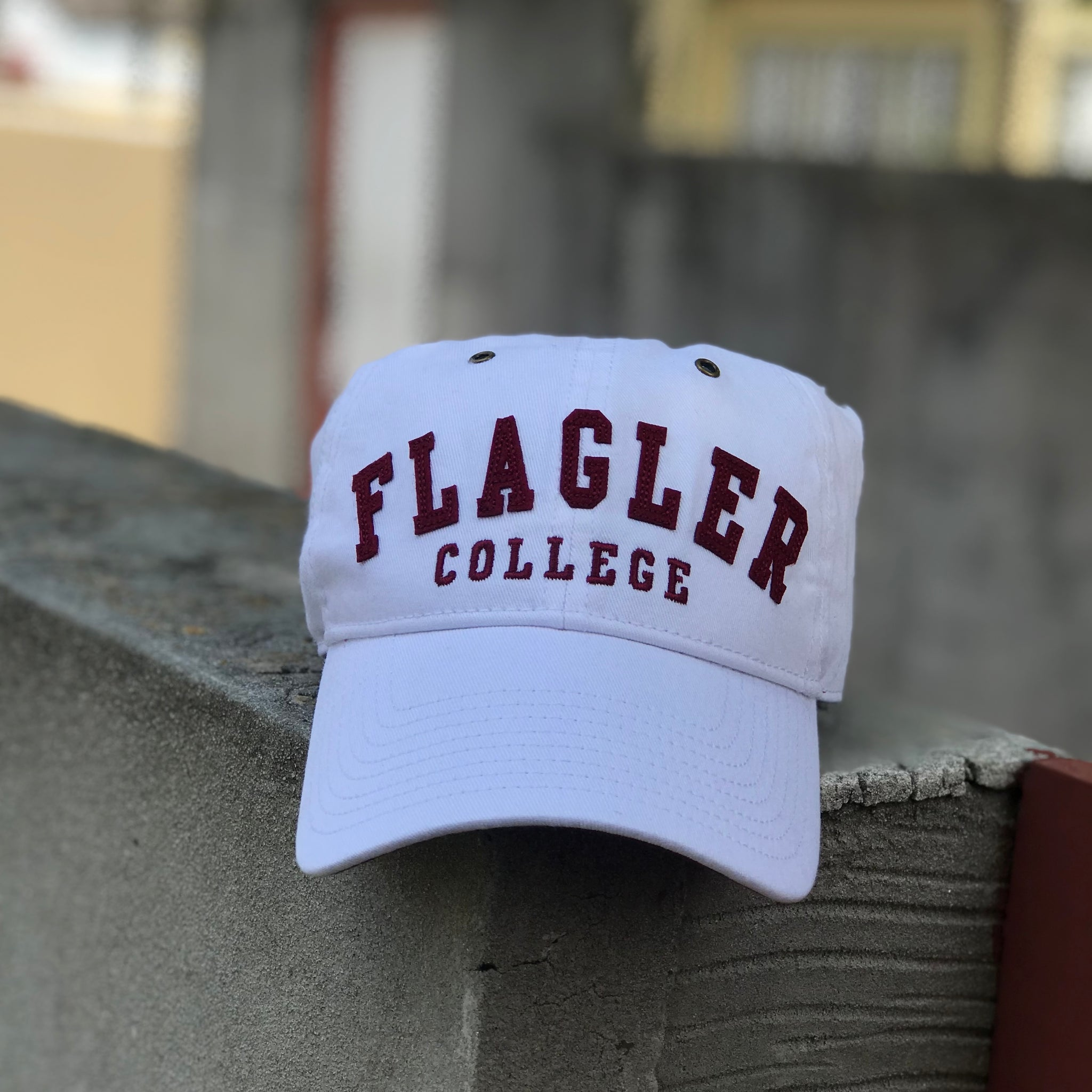white hat with Flagler College stitched on in red felt across front