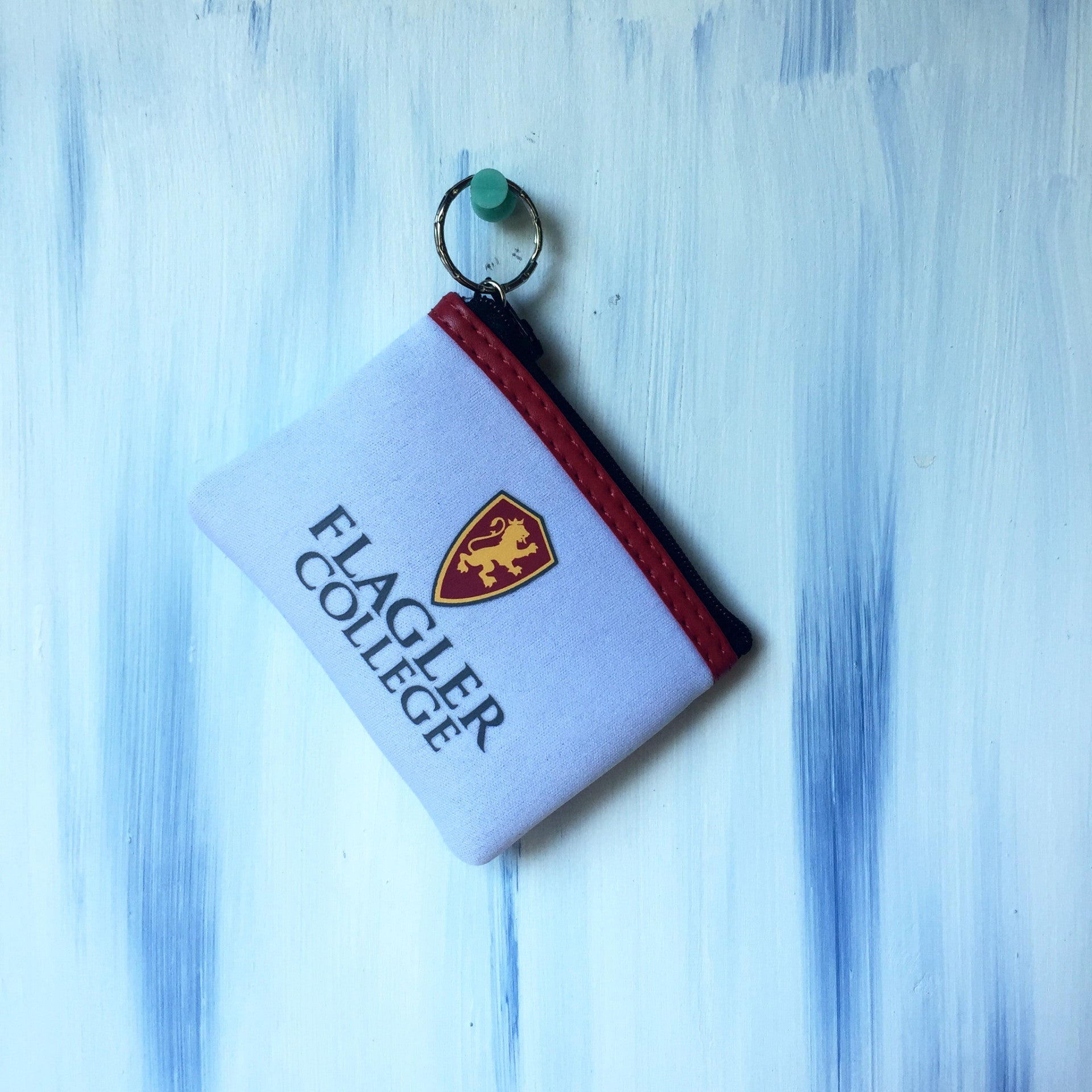small white keychain change purse with full color shield and Flagler college printed in black. the zipper is red