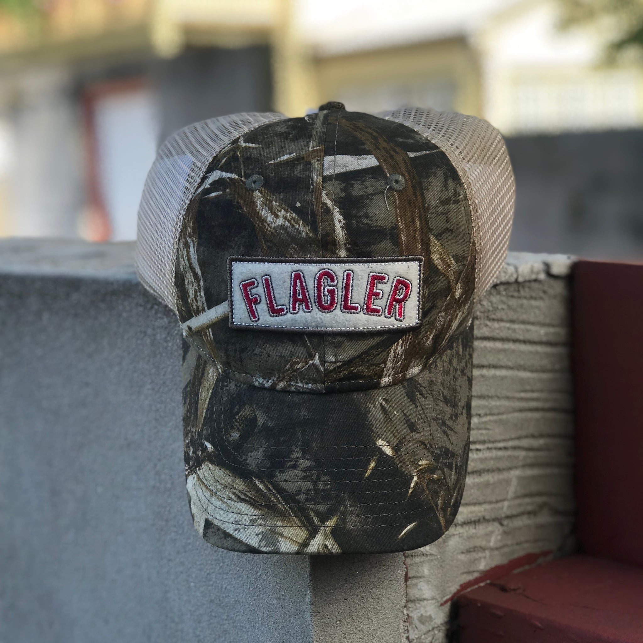 camo front with cream mesh in back. cream rectangle patch on front with flagler embroidered in red