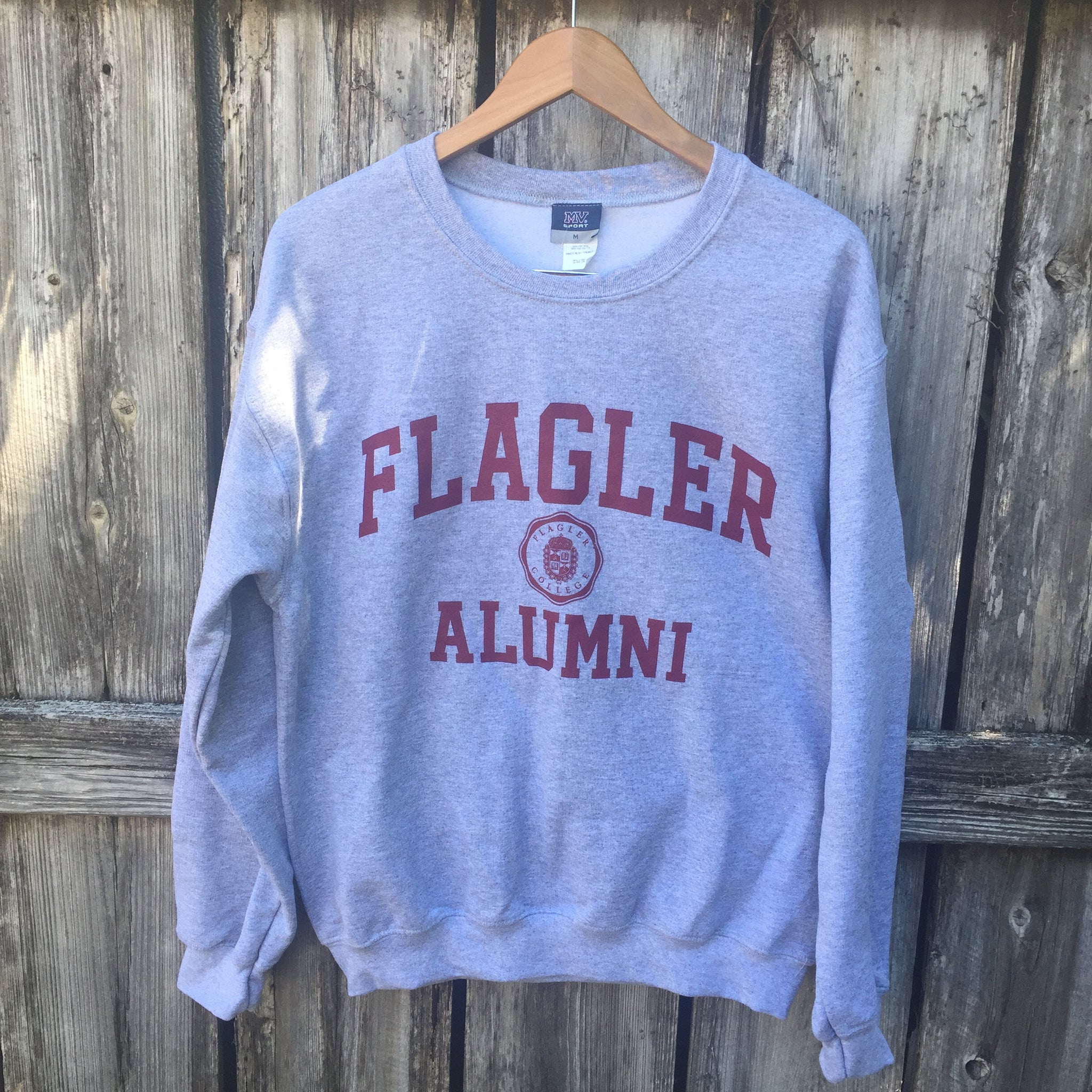 Grey crew neck with Flagler and Alumni printed in red. in between Flagler and alumni is a shield seal also in red