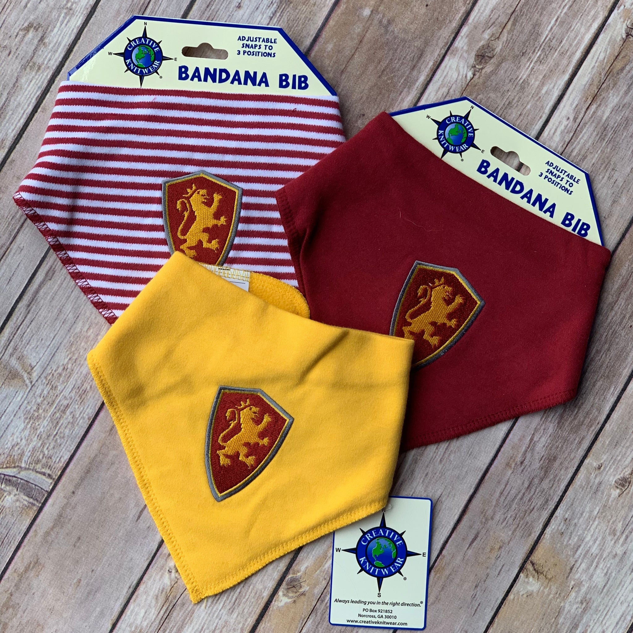 three bandanna bibs with red and yellow embroidered shield patch on front of each. The first big has red and white stripes, the second is solid yellow and the last is solid red