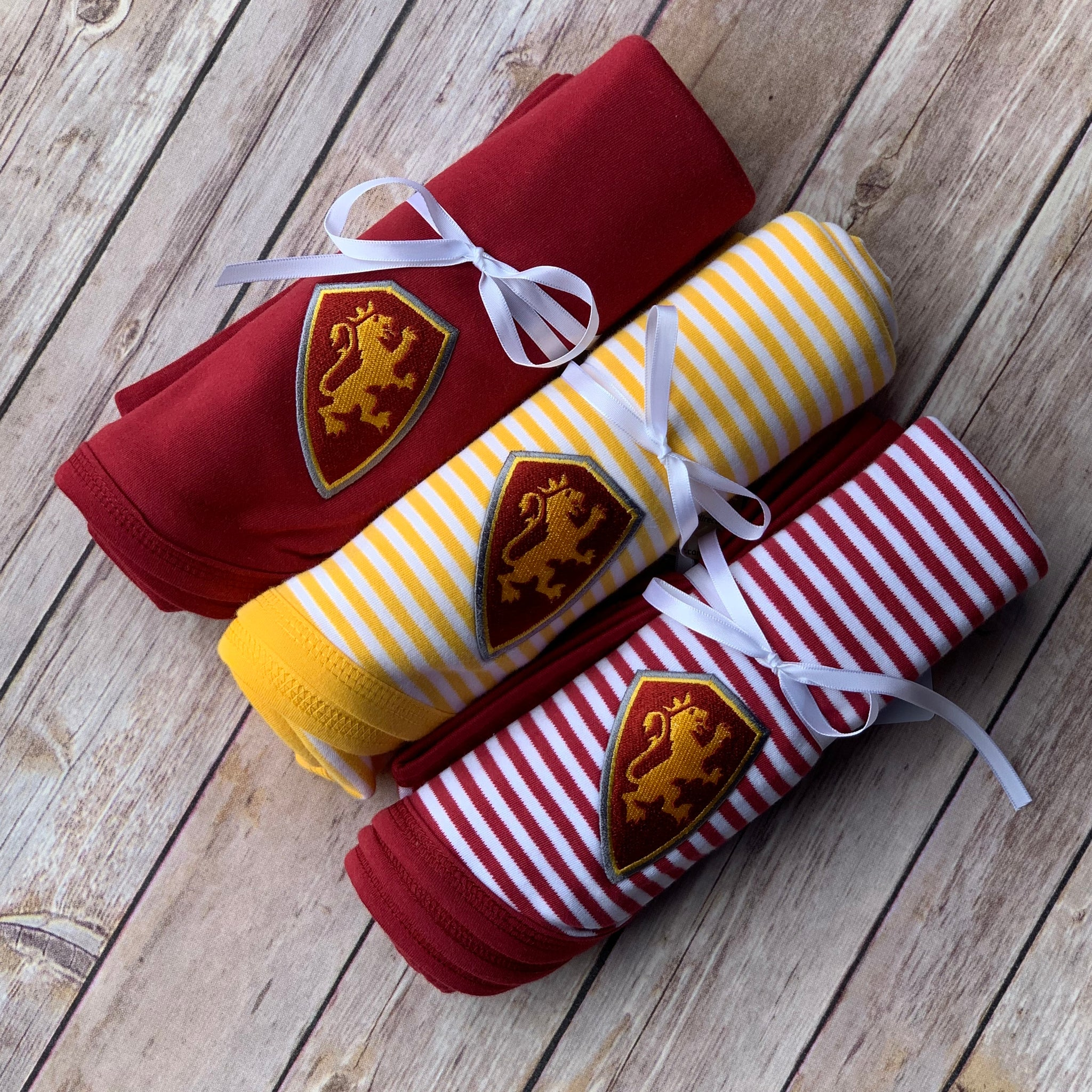 three baby blankets with embroidered yellow and red shield patch on each. one blanket is solid red, the other has yellow and white stripes and the last has red and white stripes