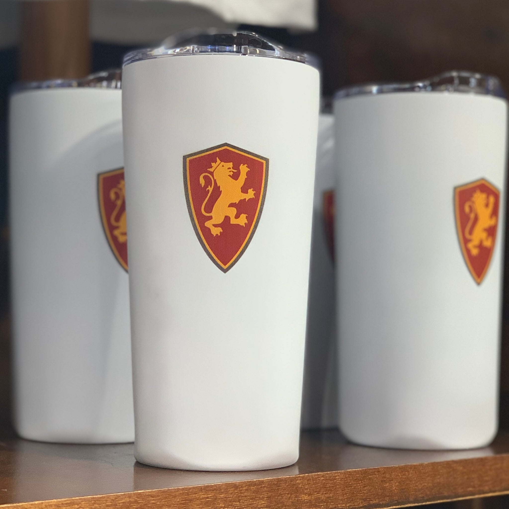 18 oz white tumbler with gold and red lion shield. lid is clear