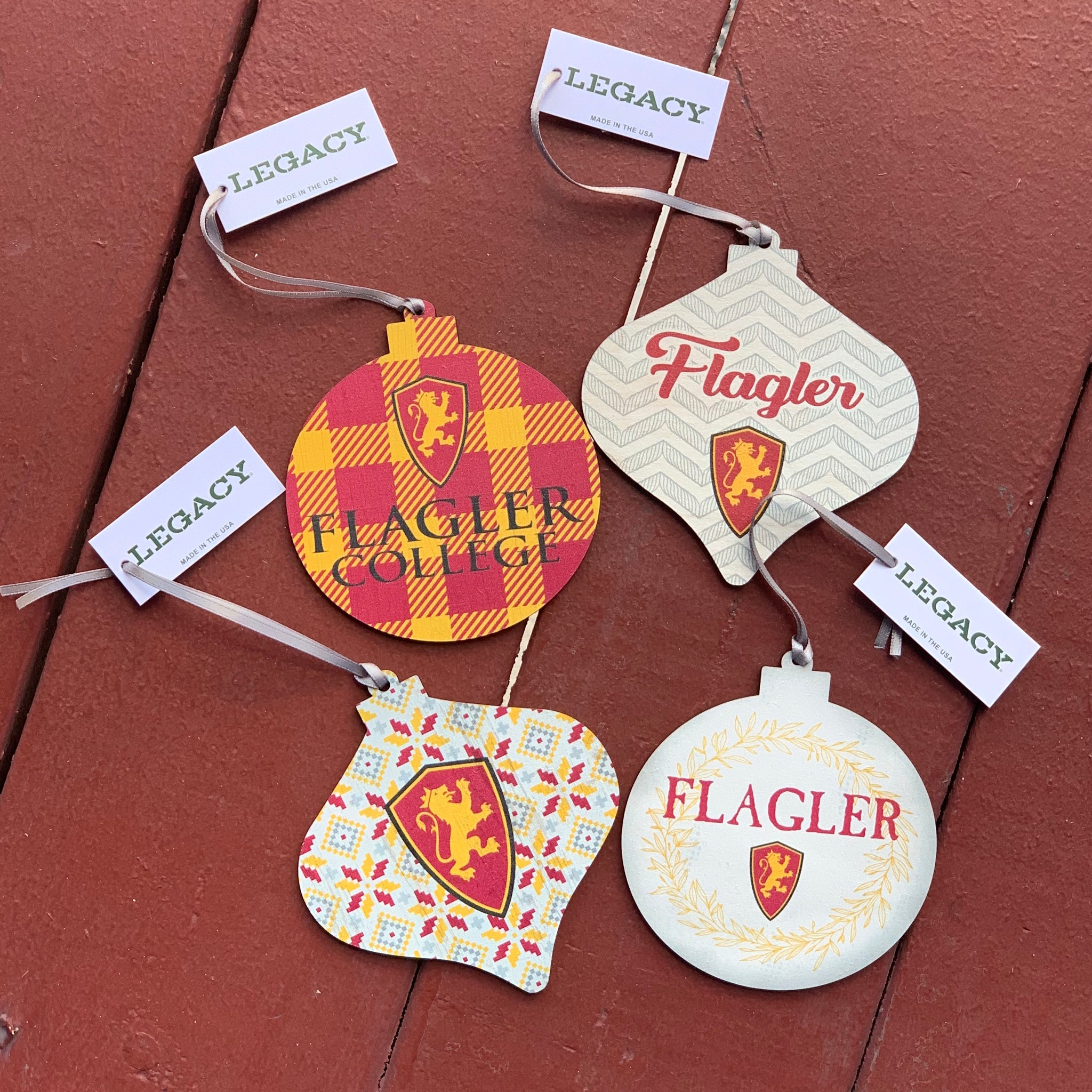 four wooden holiday ornaments in different styles. first ornament is red and gold plaid with red and gold lion shield and flagler college printed in black. Second has grey zig-zag lines with flagler printed in red cursive and red ad gold lion shield. third has red ad gold star flowers on it with large red and gold lion shield. the fourth is a cream color with a gold wreath outlining ornament and it has flagler printed in red with red and gold lion shield.