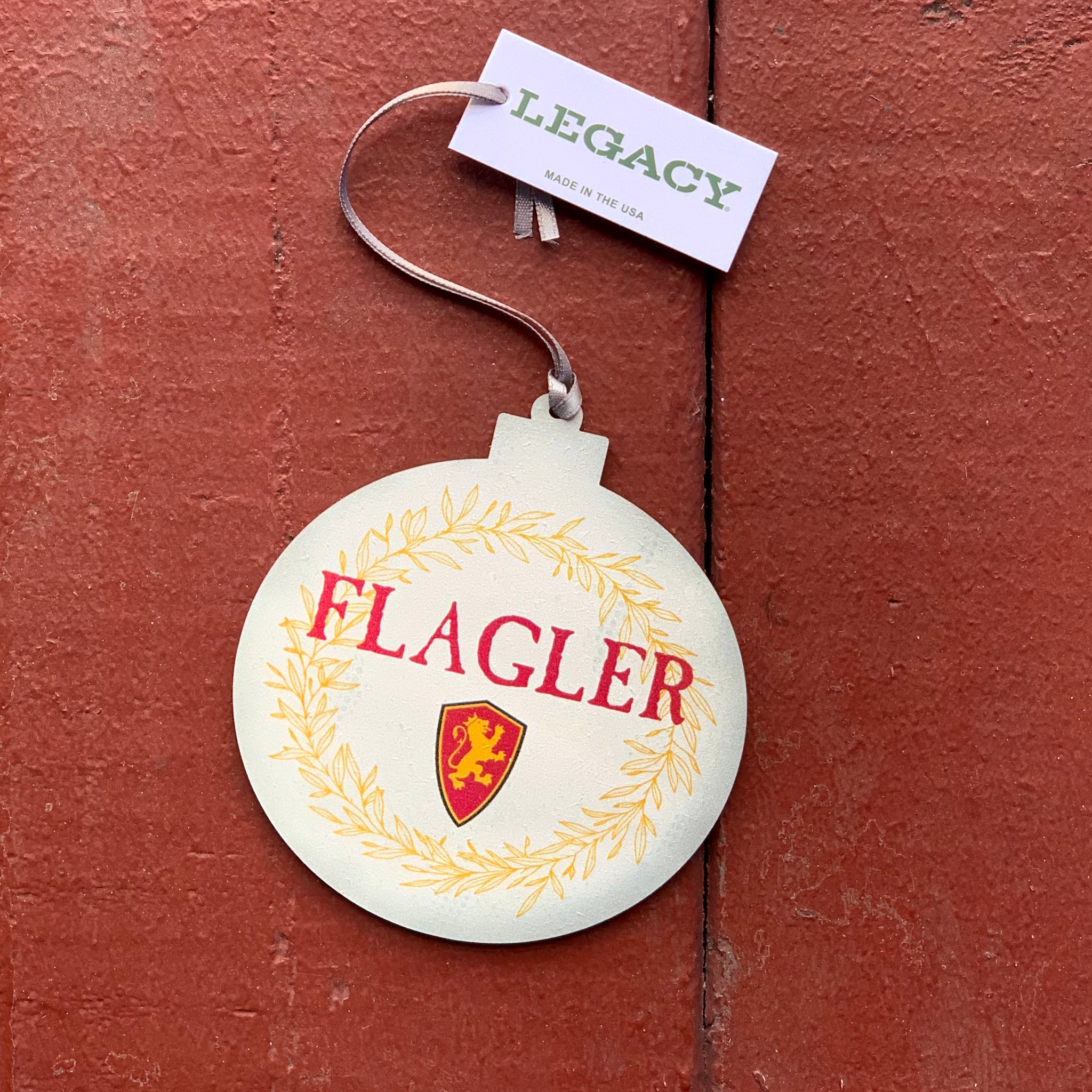 Round ornament that is a cream color with a gold wreath outlining ornament and it has flagler printed in red with red and gold lion shield