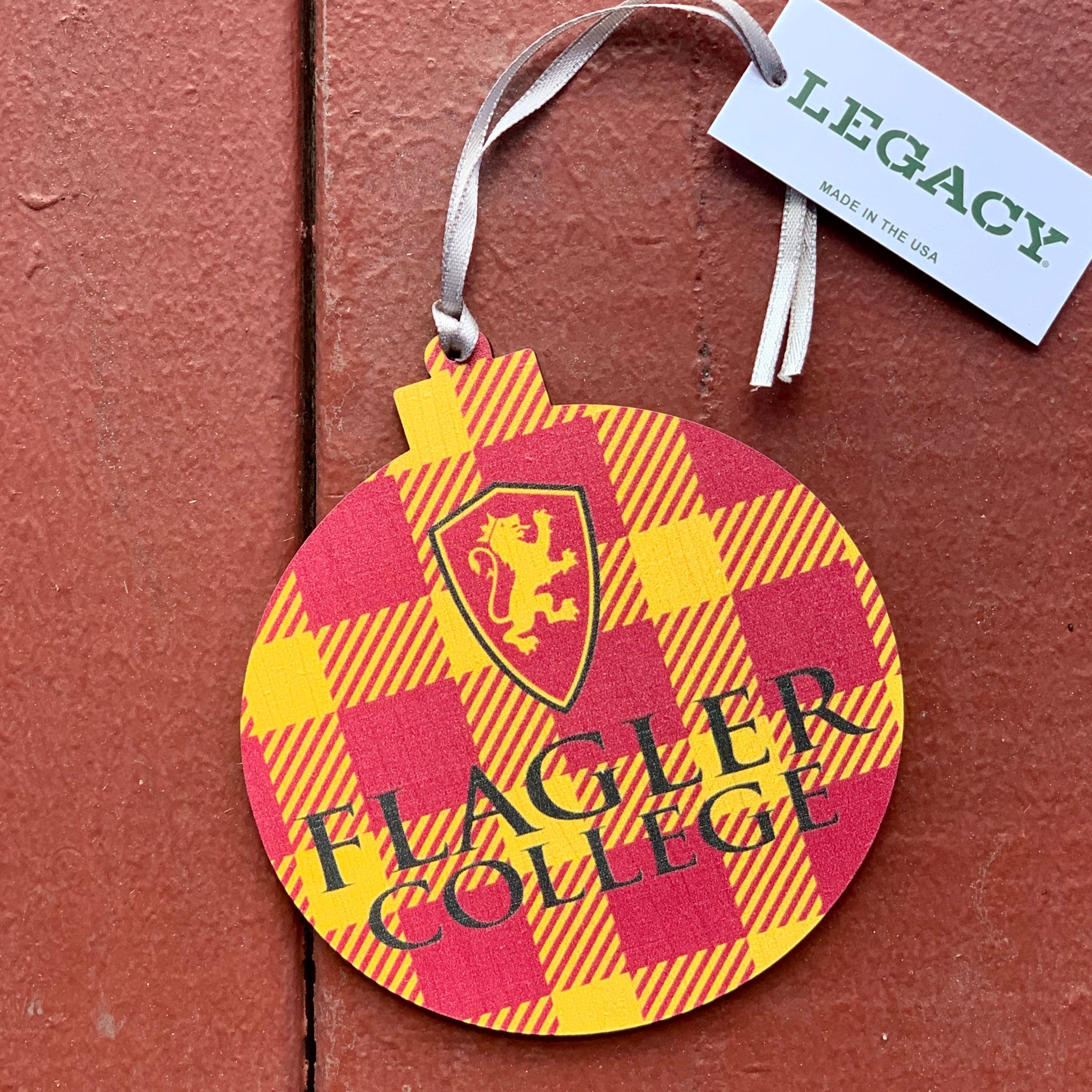 Circle shaped ornament that has red and gold plaid with red and gold lion shield and flagler college printed in black.