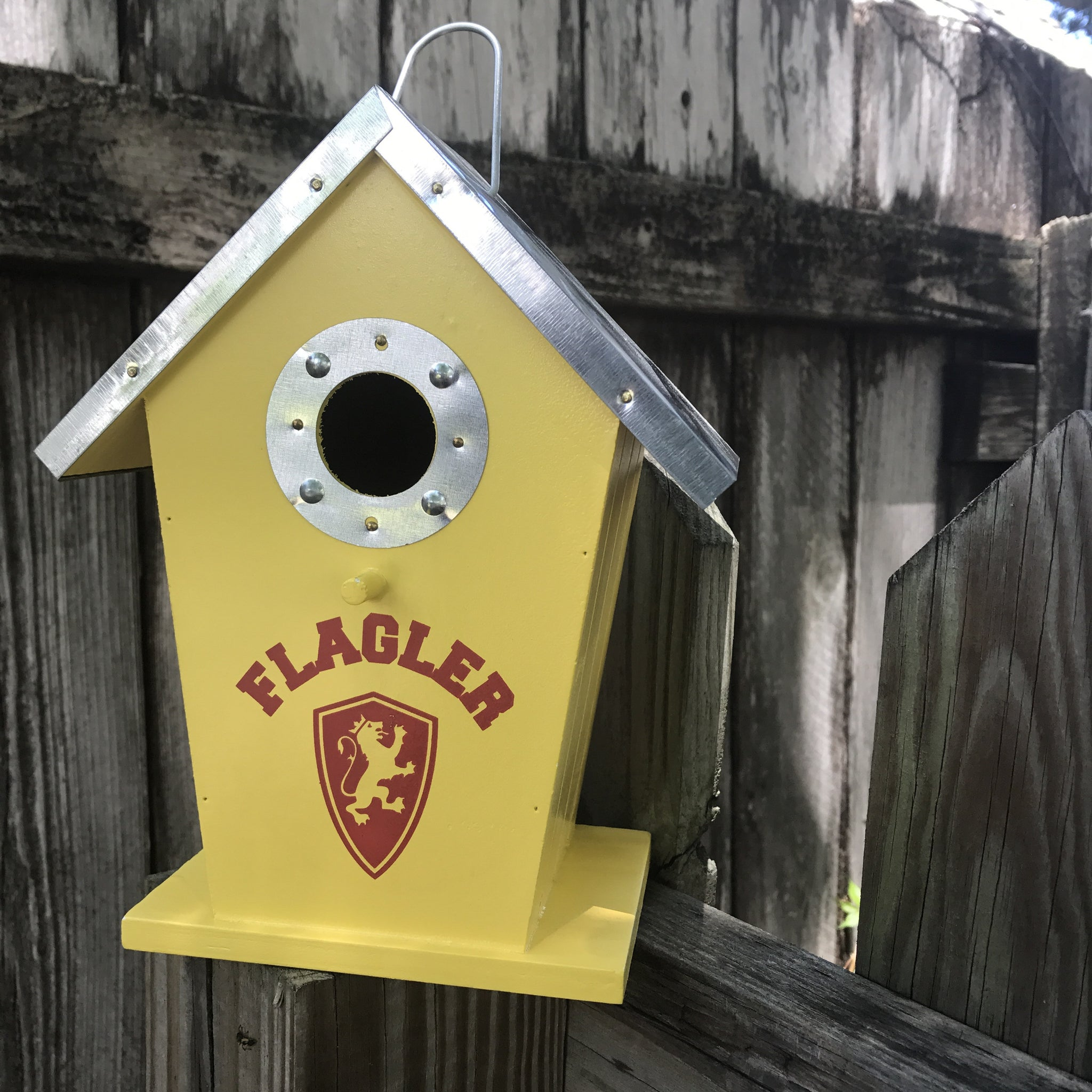 yellow birdhouse with silver roof and Flagler and shield printed in red