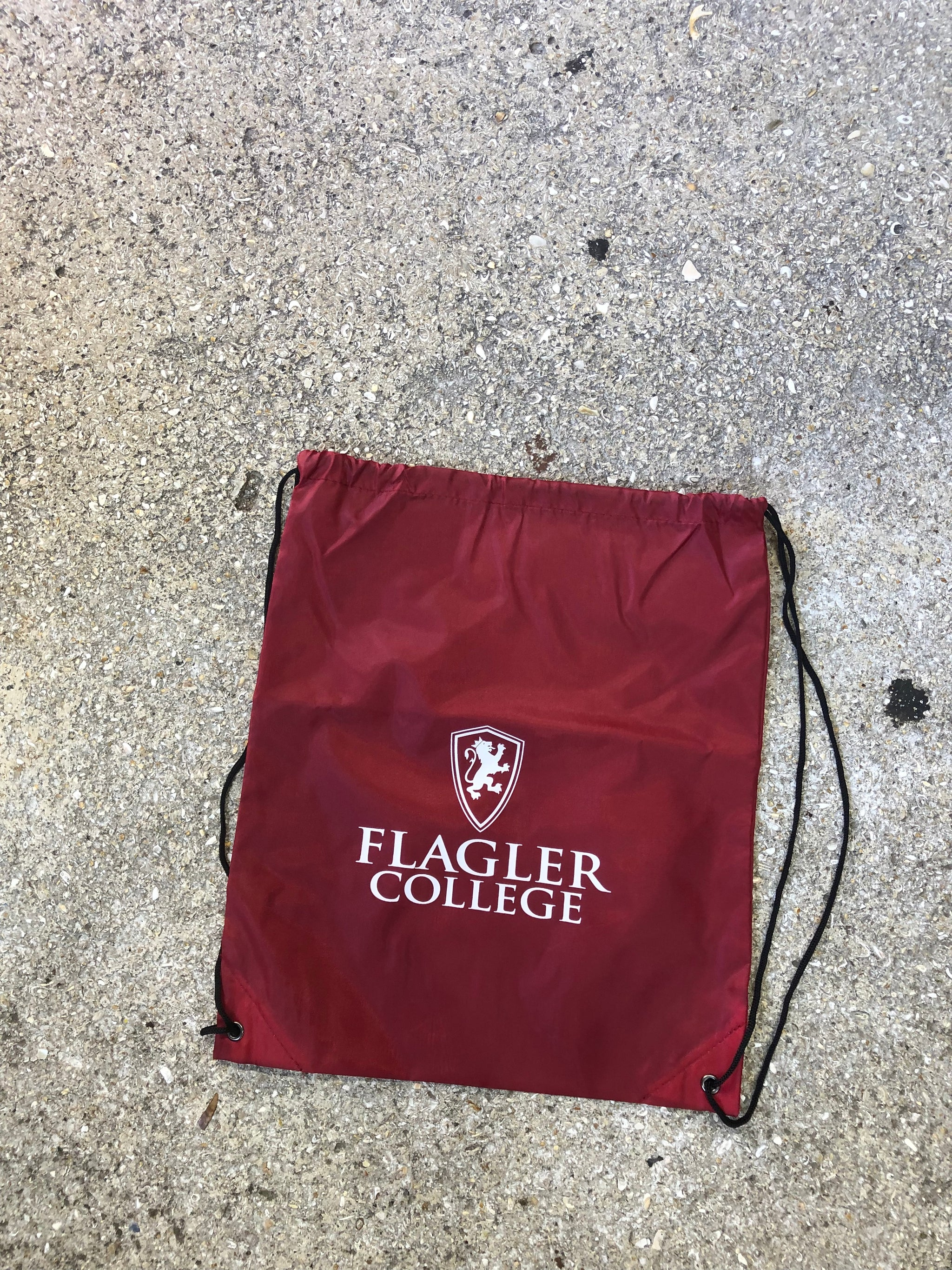 red drawstring backpack with Flagler college and shield printed in white