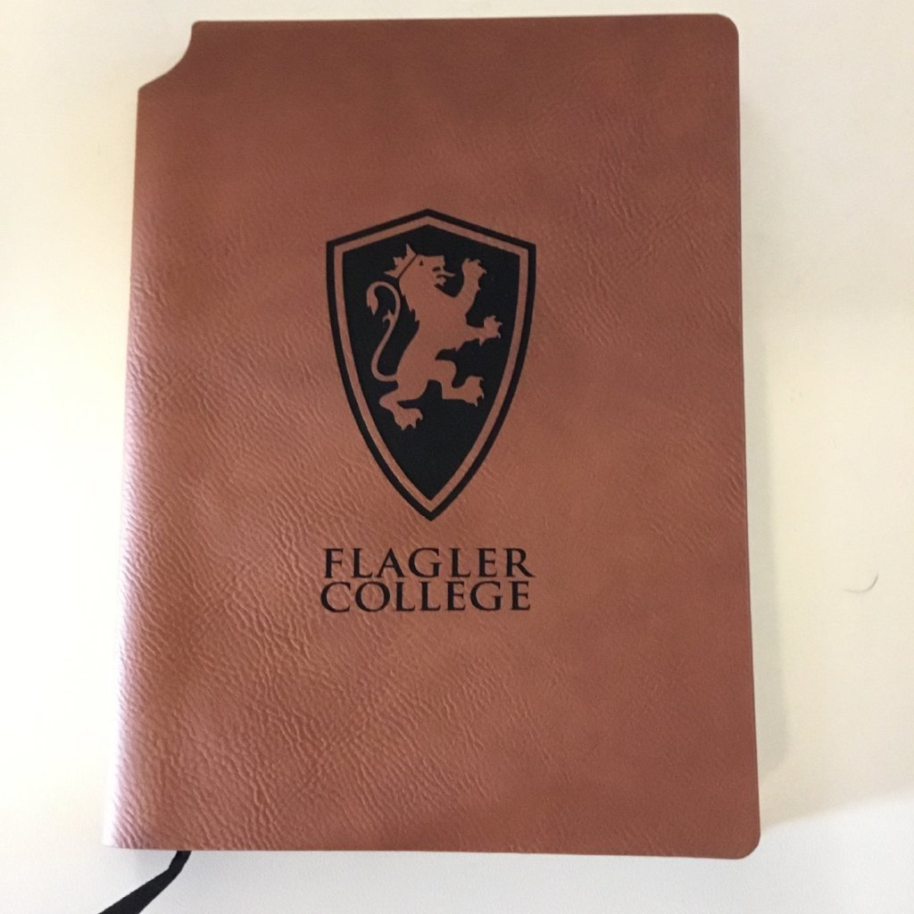 "Brown velour journal with a large lion shield and ""Flagler College"" printed in black"
