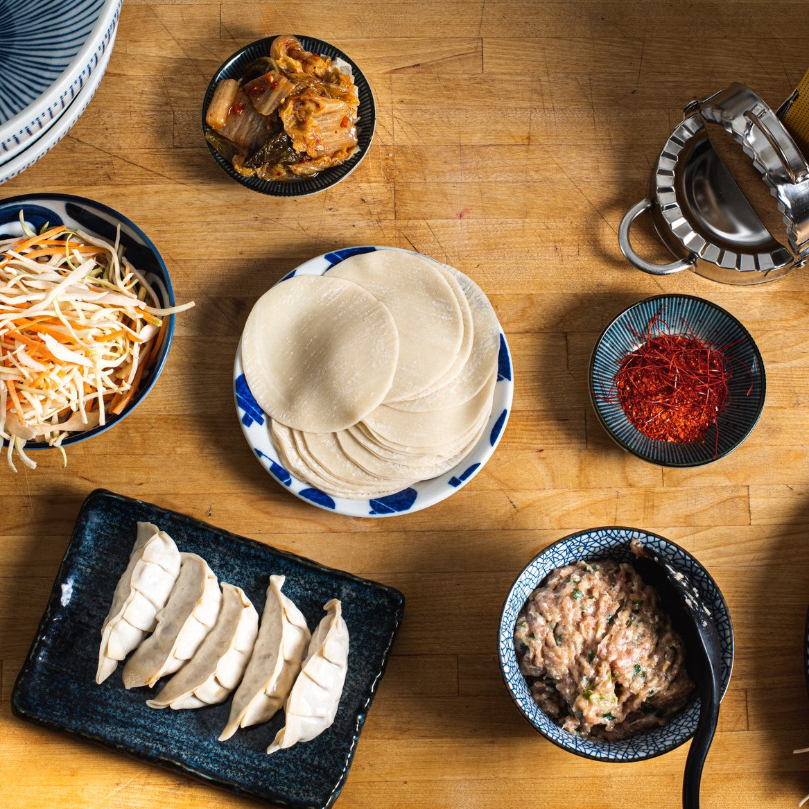 Top down view of folded gyoza and mise en place