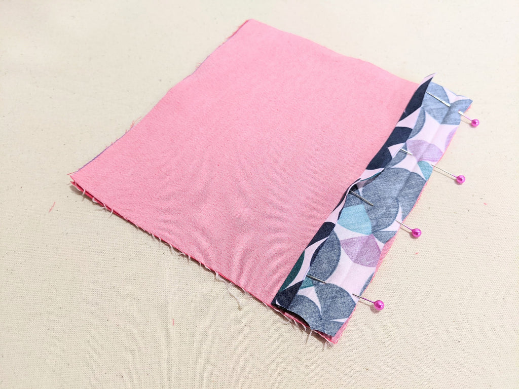 Bias tape aligned and pinned to the fabric