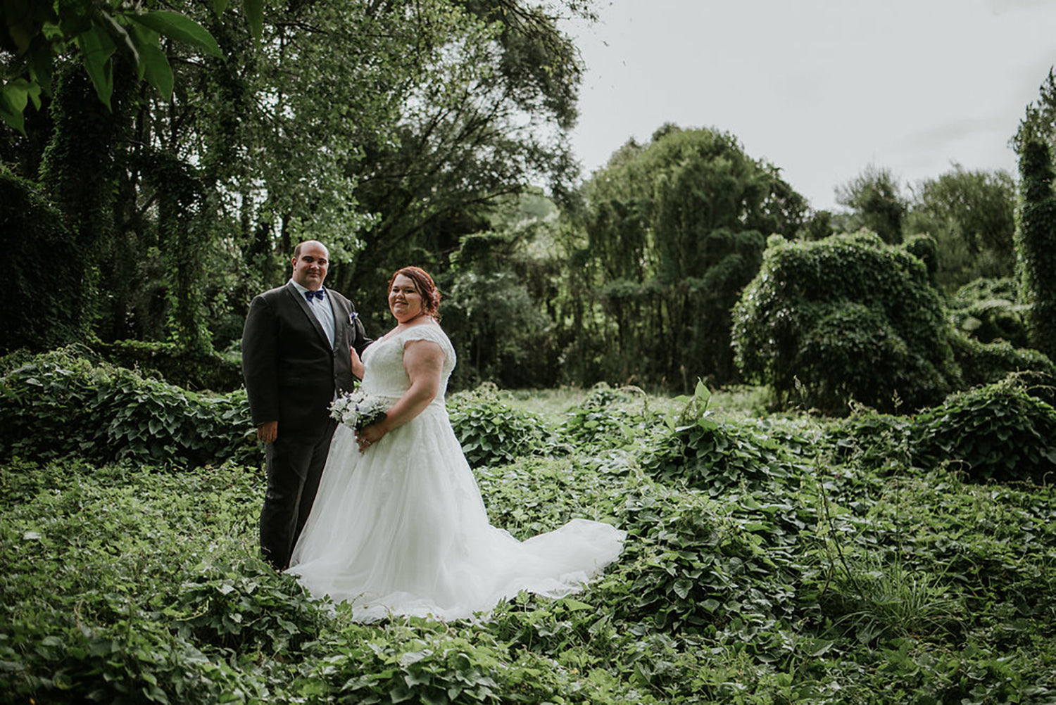 bride and groom with waitakere ranges forest in the background