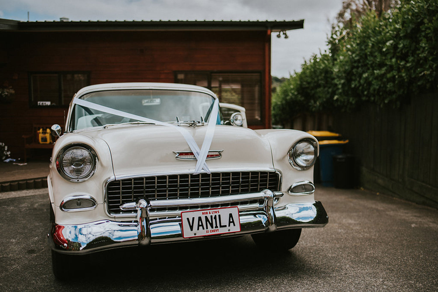 white vintage wedding car with ribbons