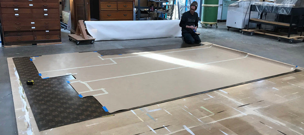 This shows the floorcloth with the paper template secured on top as a cutting guide.