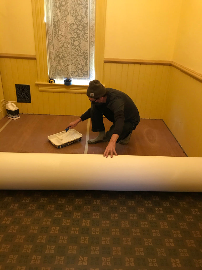 This shows the floorcloth being glued to the luan underlayment.