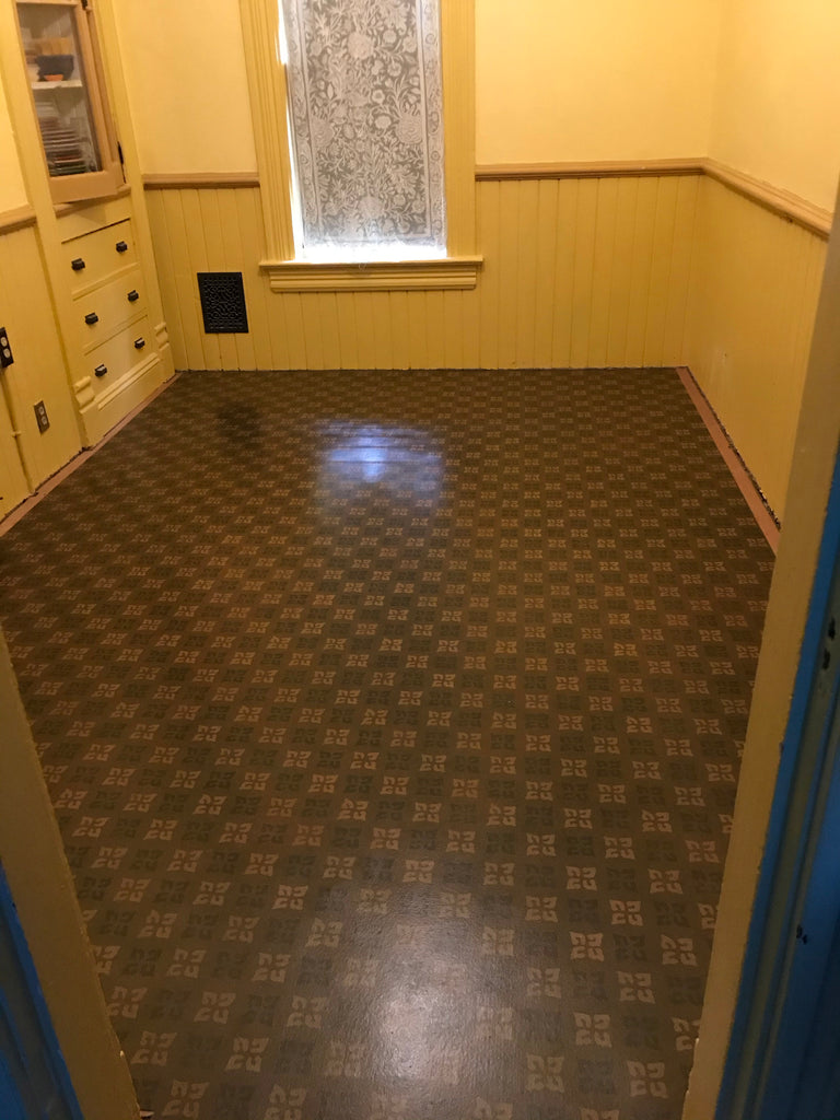 This shows the floorcloth adhered in place on the kitchen floor. A border still needs to be added around the perimeter.