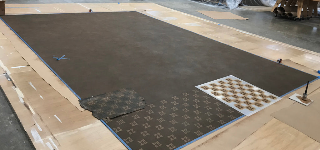 This image shows the floorcloth with the stippled background and the beginning of the first stencil pass in cream.