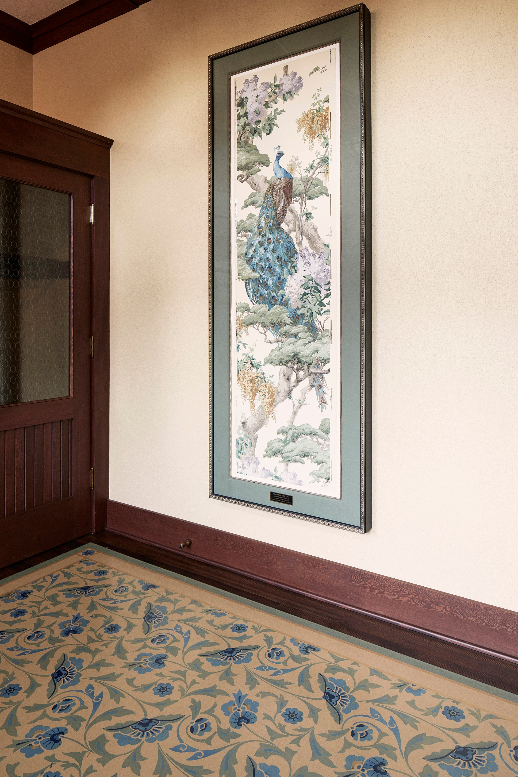 In-situ image of a shaped floorcloth, made to perfectly fit this space. The design is an all over floral pattern by Christopher Dresser. The Peacock is an original wallpaper panel c.1910 from Arthur Sanderson & Sons. Photo by Sally Painter.