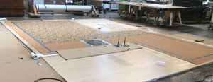 Production image of this shaped floorcloth being stenciled.