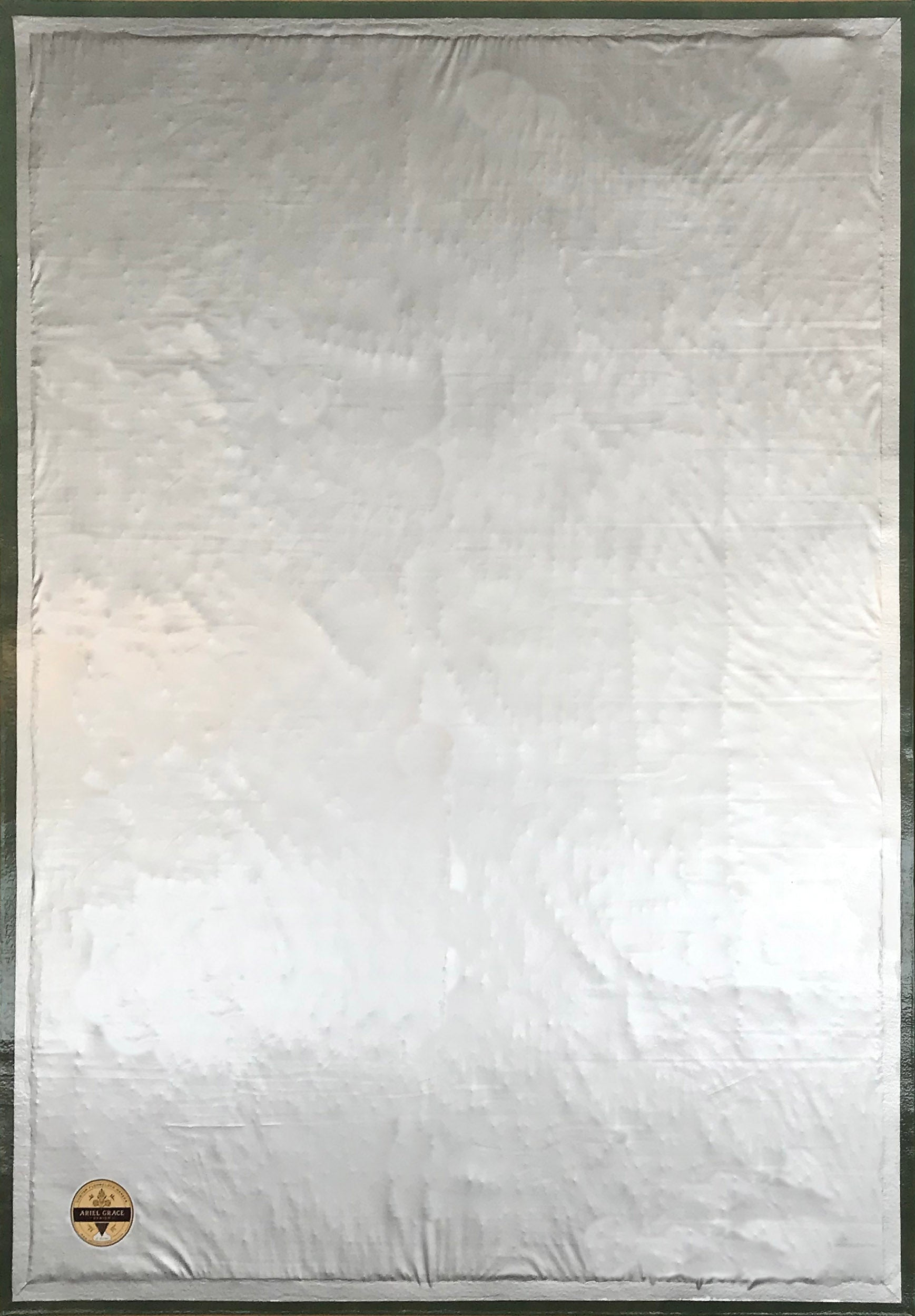 The backside of this floorcloth, showing the waterproof vinyl layer which is attached to the hem, covering a layer of carpet padding.