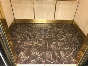 In-situ image of this floorcloth at the base of an elevator car.  The pattern emulates Emperador Dark marble tile.
