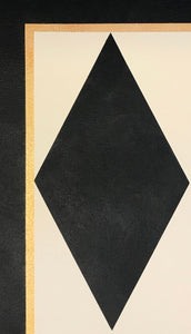 A close up of a corner of this floorcloth showing a full black diamond and border comprised of a thin gold accent line and a black band.