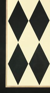 A close up image of this harlequin patterned floorcloth in a soft yellow-white and charcoal colorway.