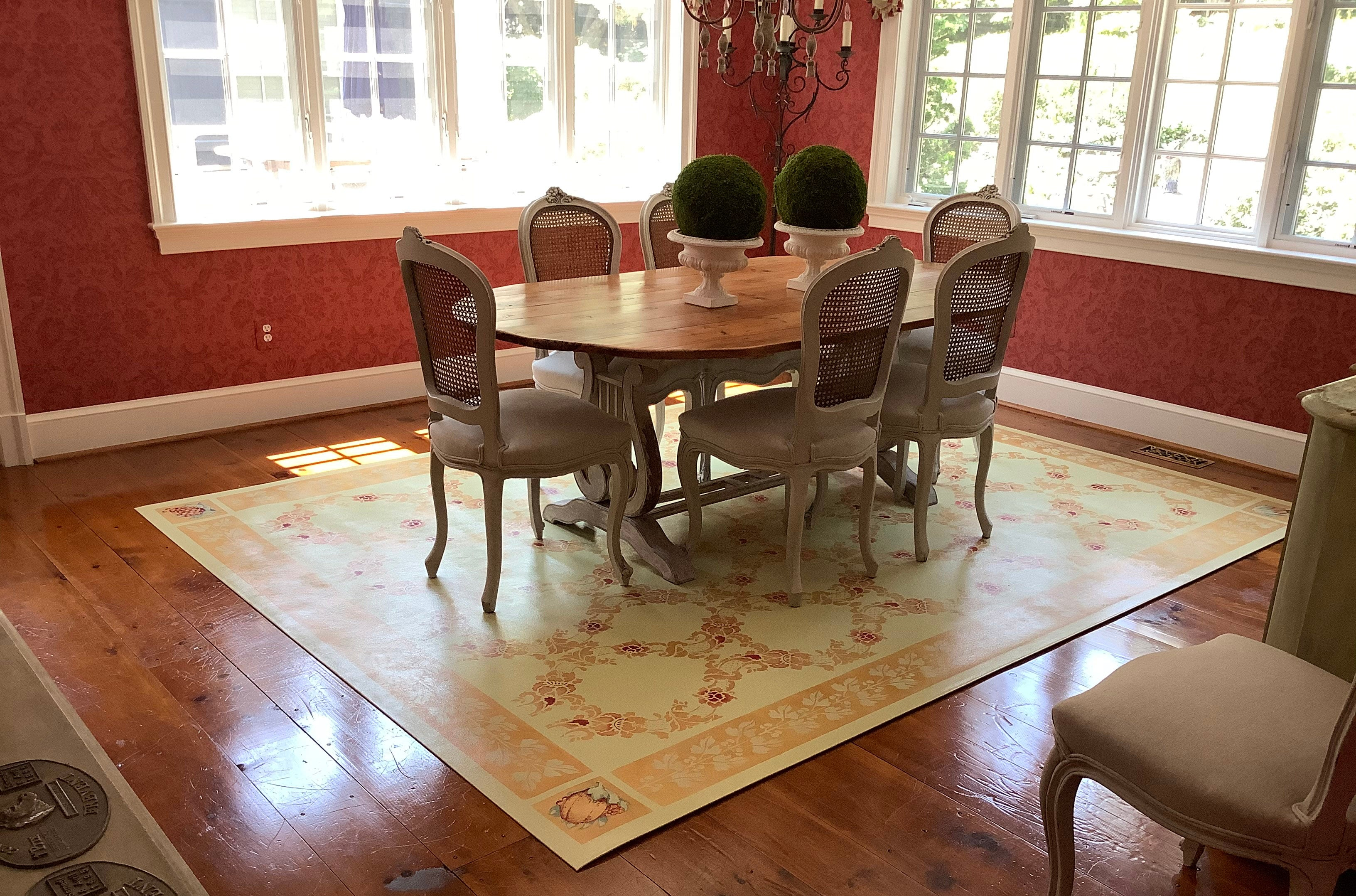 In-situ image of this custom floorcloth with a trellis-like center and border vines.