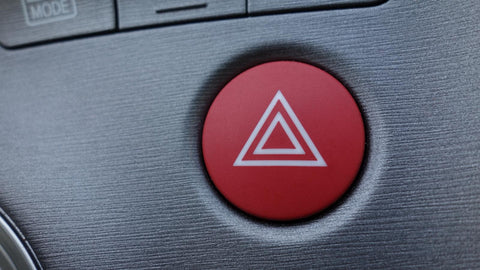 Roadside assistance needed! Hazard lights button on the dashboard of a vehicle.