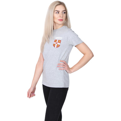 Female model wearing pale grey short sleeved T-shirt, with University of Cambridge shield in red, white, and yellow on the top left side. Brought to you by CuratingCambridge.com
