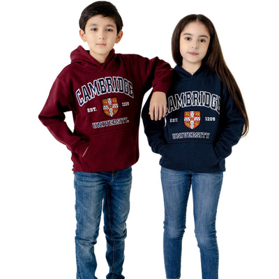 Two children in hooded sweatshirts, one maroon and one navy. Design on front of sweatshirts includes the University of Cambridge shield, lettering above and below the shield that reads CAMBRIDGE and UNIVERSITY in capitalised serif font outlined in white, and EST. 1209 in white. Brought to you by CuratingCambridge.com