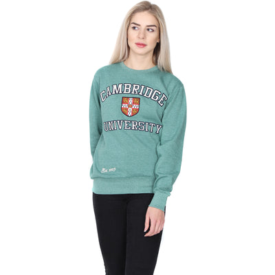 Female model wears sweatshirt in Cambridge blue (pale green). Sweatshirt has the Cambridge University coat of arms on the front, with the word CAMBRIDGE above and UNIVERSITY below, in white serif font capitals outlined in black. White italic text at the bottom right of the sweatshirt reads Est. 1209. Brought to you by CuratingCambridge.com
