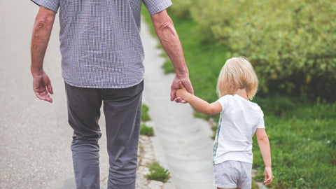 Elderly man holding a young child's hand