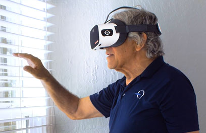 Elderly man looking out the window wearing a Vision Buddy headset