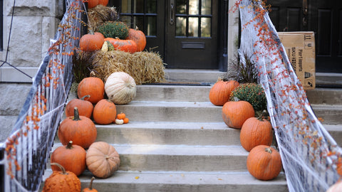 Stairs going up to a front porch decorated for Halloween with pumpkins, hay, and fake cobwebs and orange decorations on the banister