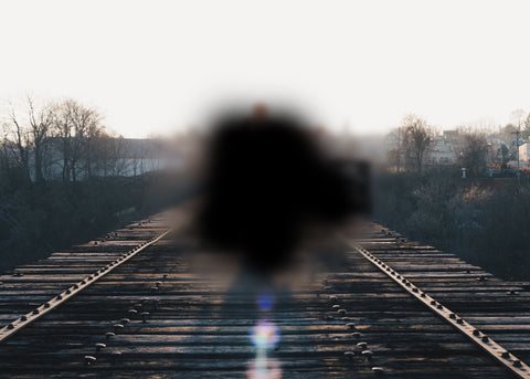 A black spot in the middle of an image of railroad tracks to roughly depict how macular degeneration can affect eyesight. Vision Buddy can help with this.