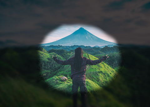A person is in the center of a beautiful mountain nature shot. The edges of the picture are blackened to simulate tunnel vision.
