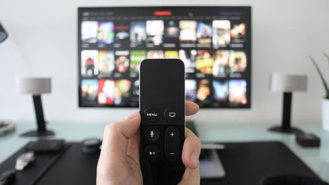 A hand holding up a small black remote control. Background is blurry with a TV screen, desk, and two small lamps.
