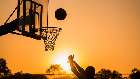 A silhouette of a basketball hoop with a basketball. It's sunset so the sky is bright orange.
