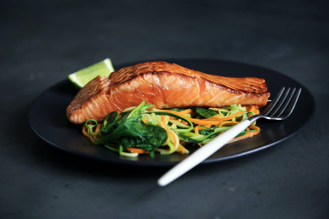 A plate of salmon on a bed of vegetables.