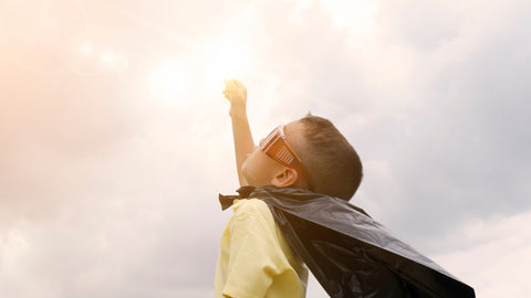 A young boy with goggles and a cape, holding his fist to the sky as if he were Superman