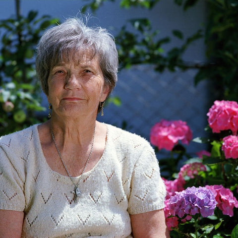 An elderly woman looking at the camera. In the background are some bushes and flowers.