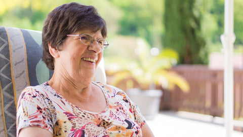 Woman wearing glasses looking off camera, smiling.