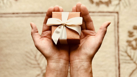 Two hands holding a small tan gift box with white ribbon and a bow
