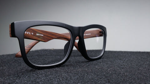 A pair of glasses that with matte black lens rims and wooden temples.