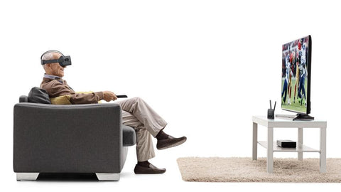Elderly man wearing Vision Buddy headset sitting on a couch and watching TV that's on a table with a rug beneath the table